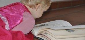 Bebê usando vestido cor de rosa deitado no chão lendo um livro