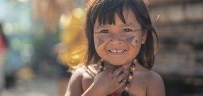 Criança indígena com desenhos em preto no rosto sorrindo