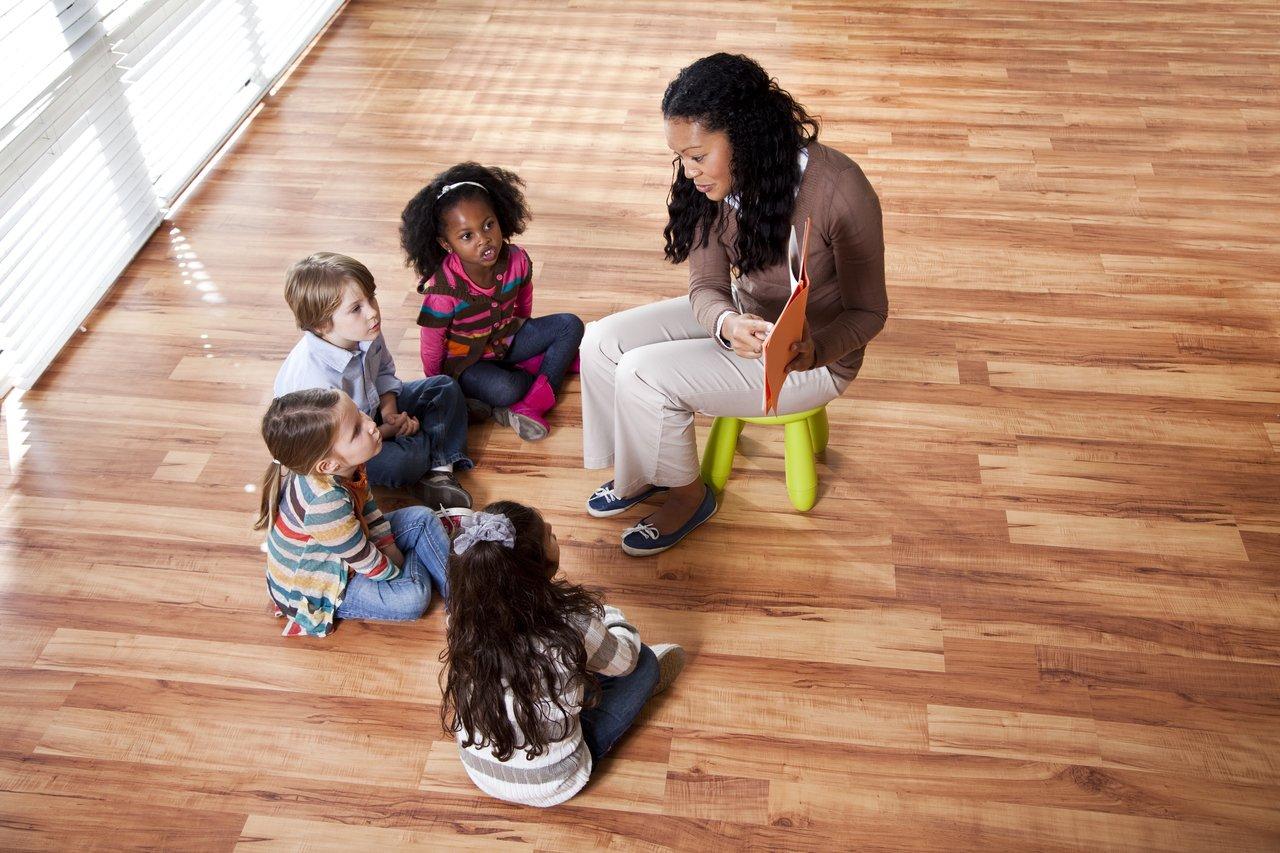 Crianças sentadas em uma roda em um chão de madeira de uma sala espaçosa prestam atenção à professora