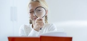 Menina loira olha atraves de uma lupa, na frente dela um livro