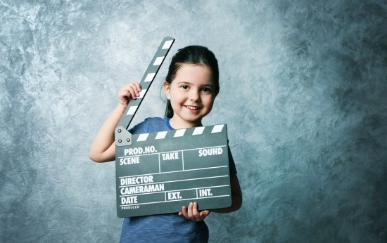 menina segurando claquete de cinema em frente a um quadro negro
