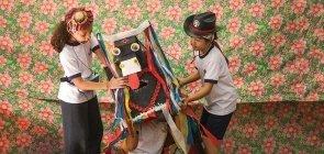Em um fundo colorido, aparece uma menina usando um microfone e uniforme segurando um boi de papelão com fitas colorida. Também segurando o boi aparece uma menina com chapeu sertanejo. Dentro da caixa do boi, uma criança aparece