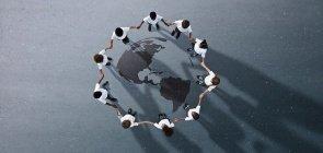 Crianças em circulo dando a mão, no centro há um mapa dos continentes