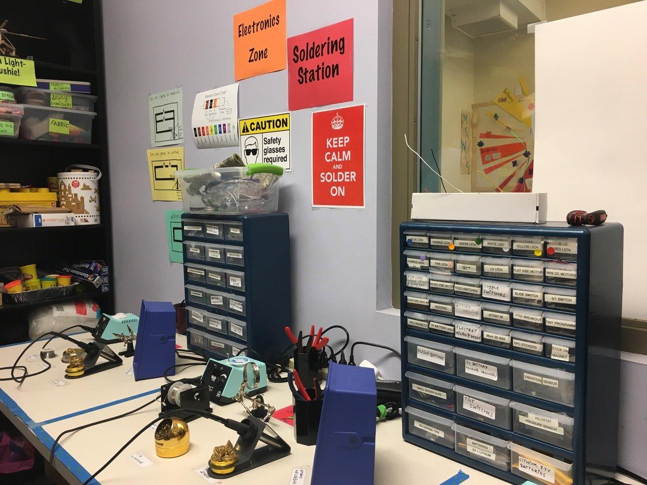 Na Acera School, há uma sala com soldas e materiais como bateriais, LEDs, papeis. os equipamentos identificados com cartazes verdes são livres para o uso das crianças. Os que acompanham indicações amarelas precisam de supervisão de um professor para serem utilizados. Os vermelhos são restritos para uso de um adulto.