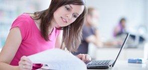 Mulher de cerca de 25 anos, sentada em uma bancada, folheando um caderno de anotações na frente do computador
