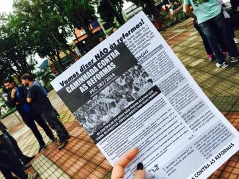 Manifestante segura panfleto contra reformas previdenciária e trabalhista