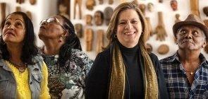 Foto da professora Nilma. Ela sorri. Ao lado dela, três alunos da EJA