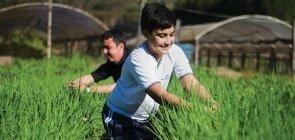 Foto de um aluno sorrindo e mexendo em uma plantação
