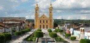 Larga praça com canteiros verdes e caminhos de cimento com igreja amarela ao fundo