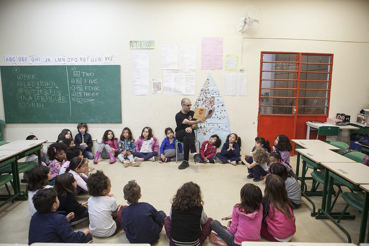 Alunos da escola municipal Desembargador Amorim Lima sentados em círculo ouvem uma história