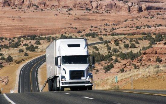 Caminhão trafega sozinho por estrada em uma paisagem de deserto