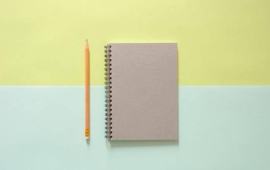 Um caderno ao lado de um lápis