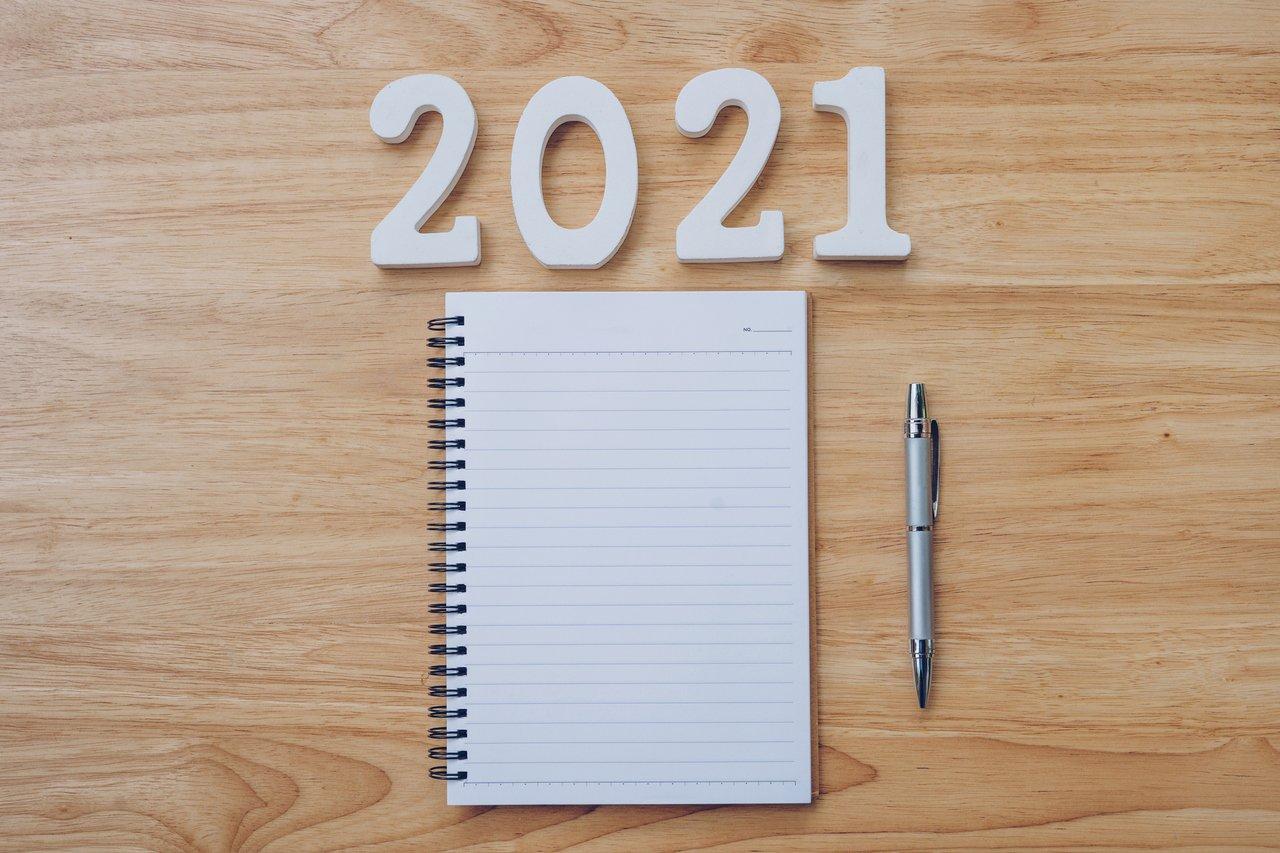 Caderno em branco sob uma mesa de escritório. Acima no letreiro escrito 2021
