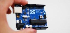 Professor segura placa de arduino usada na construção de protótipos de robótica
