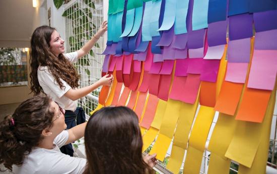Professora mostra a alunos painel com pedaços de papel coloridos