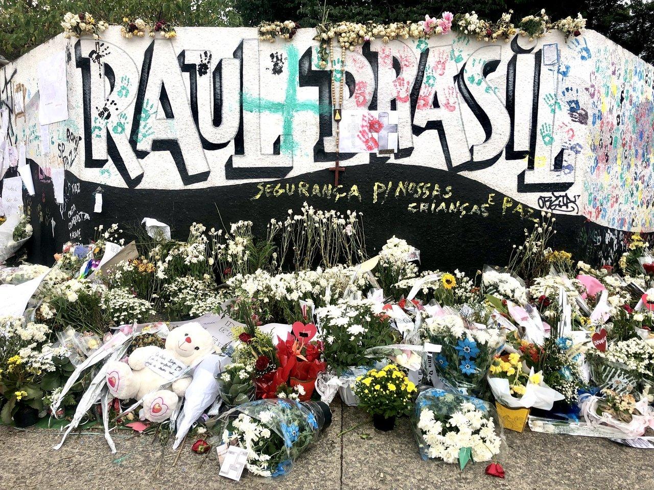Muro da escola escrito Raul Brasil com flores ao chão
