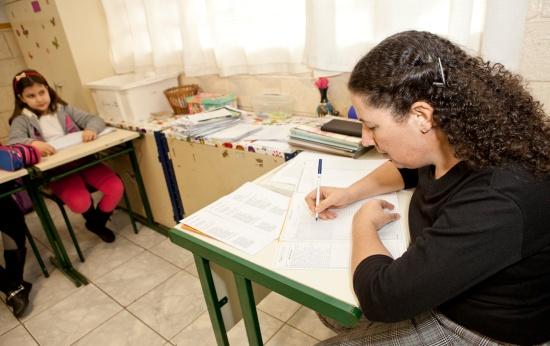Mara Mansani escreve plano de aula em sua mesa na sala de aula