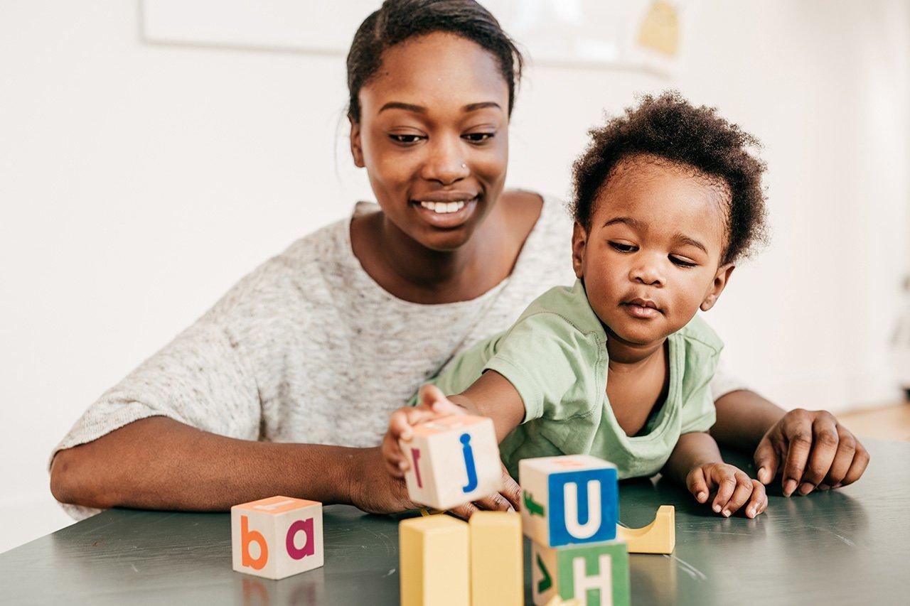 Mulher com criança no colo, criança brinca com cubos