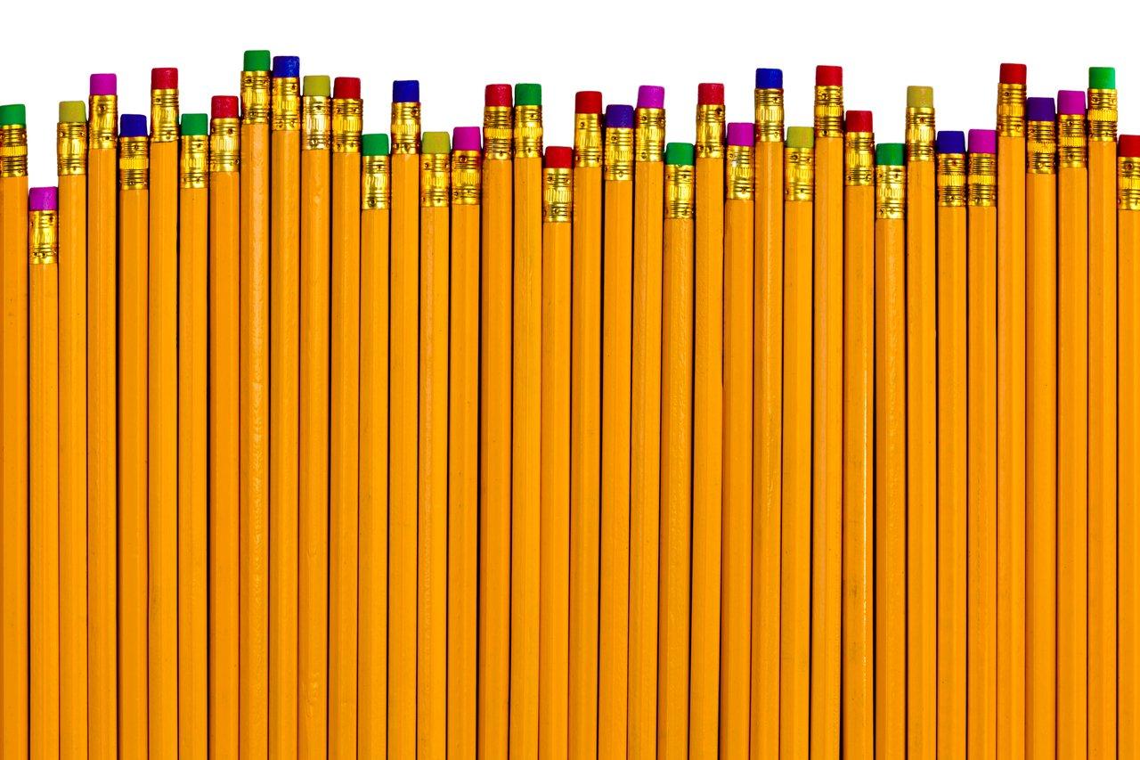 Em um fundo branco, vários lápis amarelos com borrachas de cores diferentes na ponta, estão dispostos em posições levemente diferentes