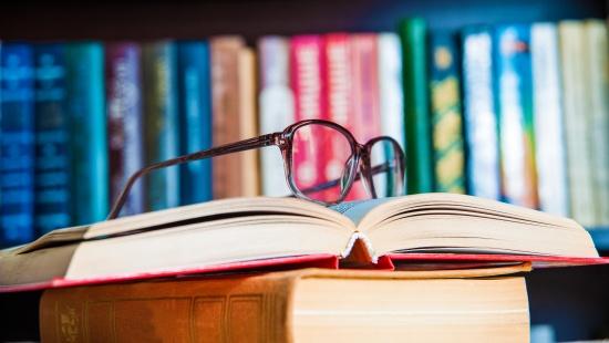 Óculos em cima de livro aberto com uma parede cheia de livros atrás