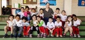 Mara Mansani sentada com sua turma de alunos da alfabetização