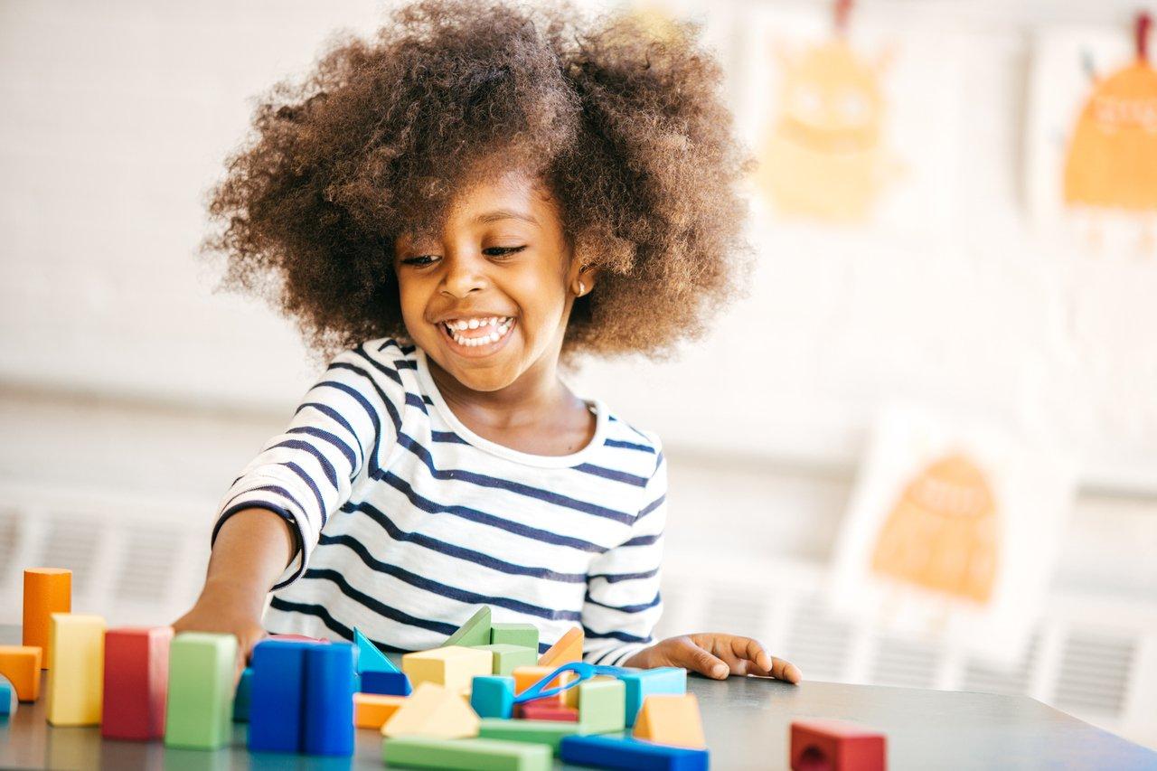 criança negra brincando com peças geométricas em casa