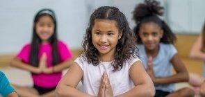Alunos praticam mindfulness ou meditação da atenção plena com professor na escola