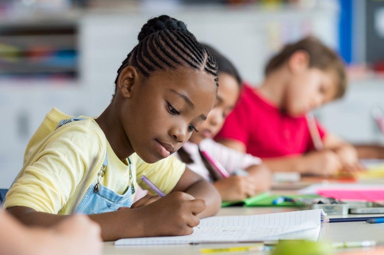 Crianças sentadas em carteiras escrevem com lápis em cadernos