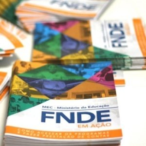 Cinco pilhas pequenas da cartilha do FNDE espalhadas de forma não linear pela mesa