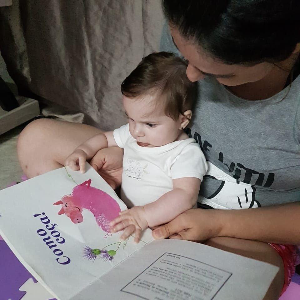 Uma bebê de 6 meses no colo de sua mãe olha para um livro aberto segurado pela adulta