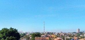 Vista panorâmica da cidade com telhados de casas e uma antena no meio da imagem