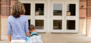 Mãe segura a mão do filho diante da entrada da escola