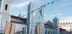 uma igreja azul e pessoas em multidão ao entorno, como se estivessem em festa