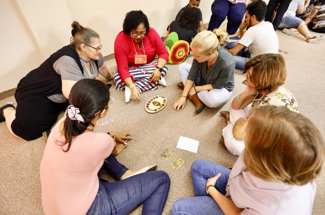 Professores de História jogam Mancala, sentados no chão