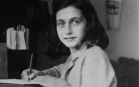 Foto preto e branca da garota alemã Anne Frank sentada em uma cadeira olhando para a foto, com um lápis na mão escrevendo em seu diário