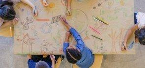Um grupo de cinco crianças pequenas vistas de cima desenhando em torno de um papel pardo