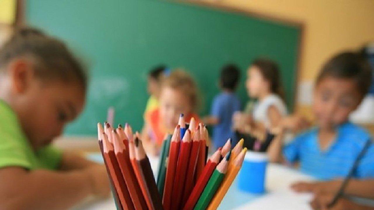 Alunos no plano de fundo escrevem sentados juntos em volta de uma mesa, lápis coloridos no primeiro plano