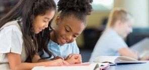 Duas meninas sentadas em uma mesa de sala aula olham um livro e sorriem
