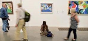 Mulher sentada no chão de um museu, ela está olhando para uma pintura