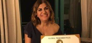 Uma mulher de cerca de 45 anos segurando um certificado do Global Teacher Prize