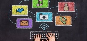 Um fundo imitando textura de lousa. Um par de mãos está sobre essa textutura em que está desenhado em giz um teclado de computador e alguns símbolos como o de música, email e redes sociais