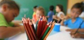 Crianças do Ensino Infantil usam lápis de cor para desenhar ao redor da mesa