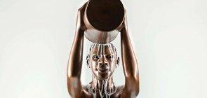 Estátua de bronze, um homem oga um balde de tinta branca em si