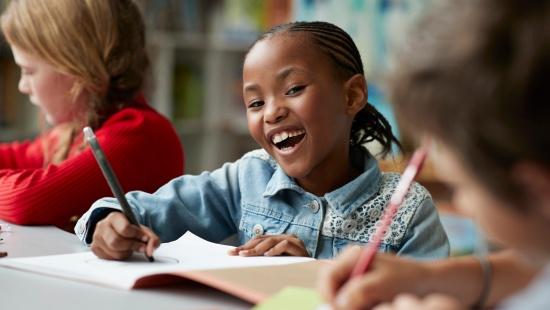 Menina negra sorri ao lado de colegas segurando lápis em frente à mesa com folhas de sulfite espalhadas