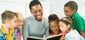 Professora sentada no chão sorri e mostra livro para alunos que a cercam