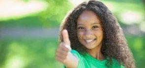 Menina mostra polegar para cima em sinal de otimismo