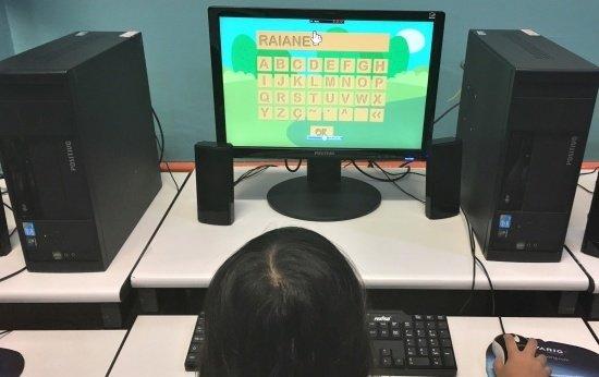 Menina escrevendo o próprio nome no computador