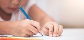 Criança escrevendo — mão com o lápis