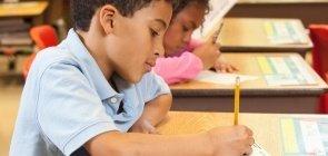 aluno sentado na cadeira escrevendo na prova