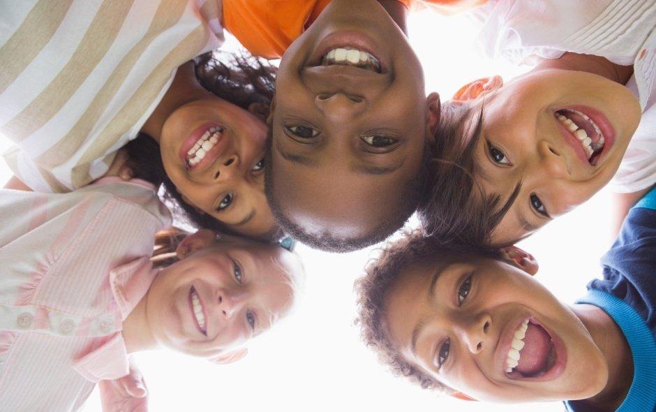 Três crianças negras e duas crianças brancas abraçadas brincando
